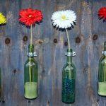 Bottiglie di vetro utilizzate come vasi con sabbia colorata